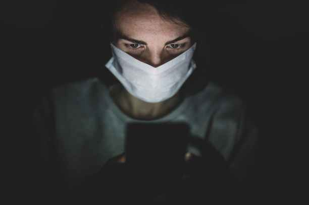 man wearing face mask using his phone in the dark